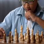 Boy with glasses playing chess