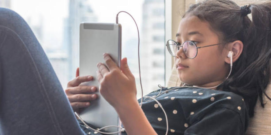 Girl with glasses reading on tablet and listening with earbuds.