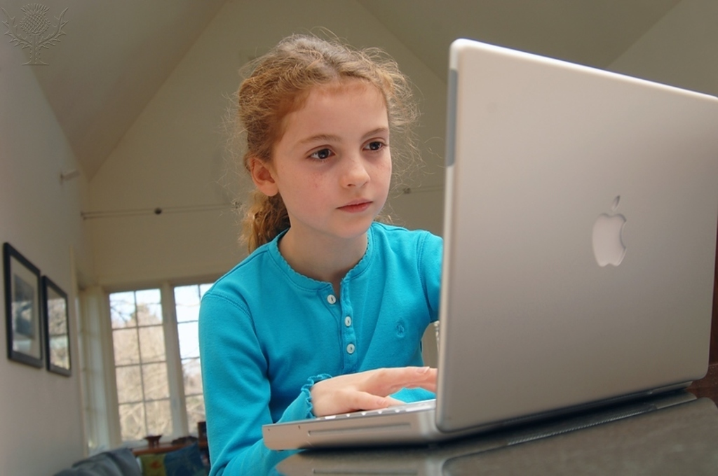 Girl using an Apple laptop computer at home.